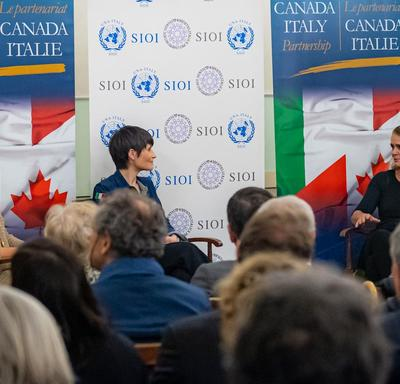 The Governor General is sitting on stage beside Italian astronaut Samantha Cristoforetti.