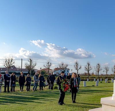La gouverneure générale se tient devant un monument au Cimetière de guerre canadien de Villanova.