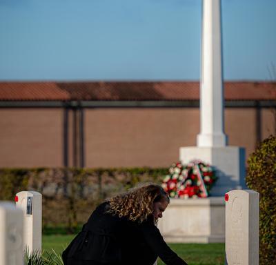 Le gouverneur général dépose des fleurs sur une tombe.