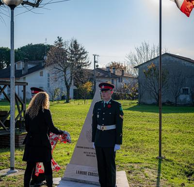 The Governor General lays a scarf on a monument at the Villanova Canadian War Cemetery.
