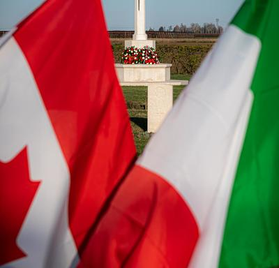Photo of Canadian and Italian flags in the Villanova Canadian War Cemetery.