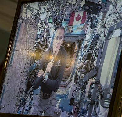Canadian Space Agency astronaut David Saint-Jacques is on a television screen talking from the International Space Station.