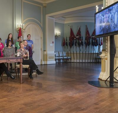 The Prime Minister, the Governor General and David Saint-Jacques`s wife, Véronique Morin, are sitting around a table looking at a television screen. A group of students are behind them.