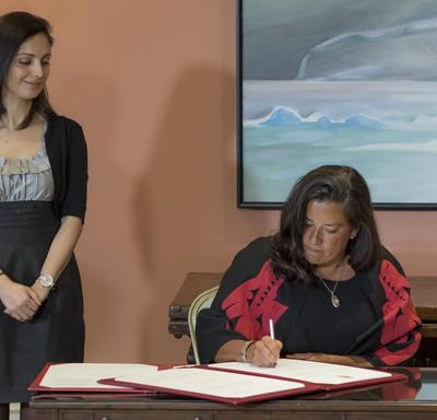 A lady sitting at a table is signing a document while a lady watches over her right shoulder.