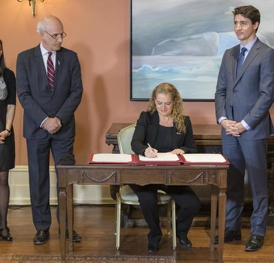 Governor General Julie Payette is sitting at a table, signing a document while a lady, the Privy Council Clerk Michael Wernick and Prime Minister of Canada Justin Trudeau watch her, standing.