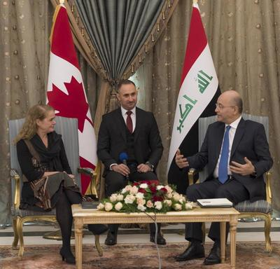 Governor General Julie Payette and His Excellency Barham Salih, President of Iraq are speaking to each other. An interpreter is sitting between them. The flags of Canada and Irak are in the background.