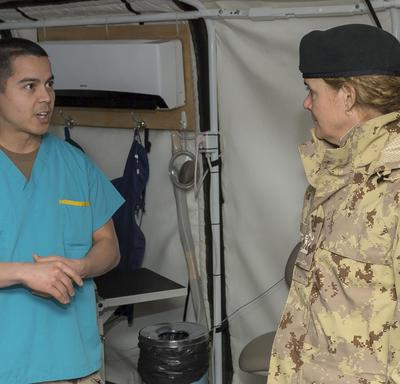 Governor General Julie Payette talks to a CAF member in medical gear.