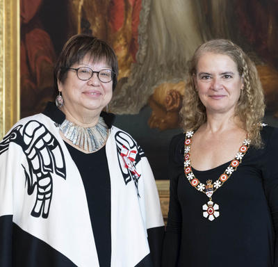 The Governor General stands next to Judith Sayers.  Both are wearing their Order of Canada insignia.