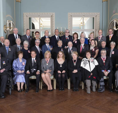 A group photo of the 35 people invested into the Order of Canada with Governor General Julie Payette. They are arranged in three rows, the first sitting and the others standing.