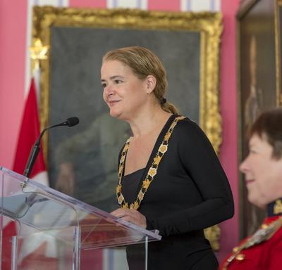 La gouverneure générale prend la parole à une podium et prononce un discours.  La commissaire de la GRC, Brenda Lucki, est assise au premier plan de la photo.