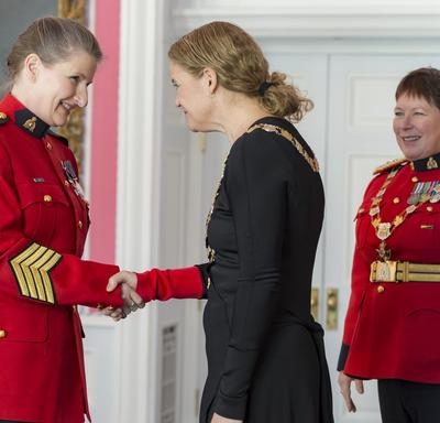 Diane L. Cockle shakes the Governor Generals hand.  Standing behind them to the right is RCMP Commissioner Brenda Lucki.  All three are wearing their insignia.