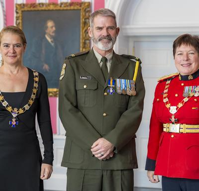 Luc Gagnon pose avec la gouverneure générale et la commissaire de la GRC Brenda Lucki.  Tous les trois portent leur insigne.