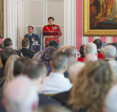 RCMP Commissioner Brenda Lucki stands on a stage in front of a podium facing a room filled with people.  She delivers a speech as the Governor General, seated on stage,  looks at her.