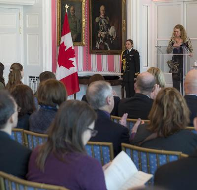 The Governor General is speaking from a podium. The audience is listening to her.