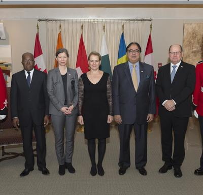 A groupe photo of the four news heads of mission with the GOvernor General.  They are flanked by ceremonial guards and stand in front of a series of flags representing each country.