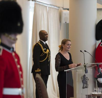 The Governor General stands in front of a podium and delivers a speech.  On either side of her are ceremonial guards.  Behind her, is her Aide-de-camps.