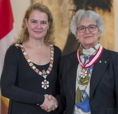Louise Nadeau stands next to the Governor General.  Both smile at the camera.  They are wearing their Order of Canada insignia.