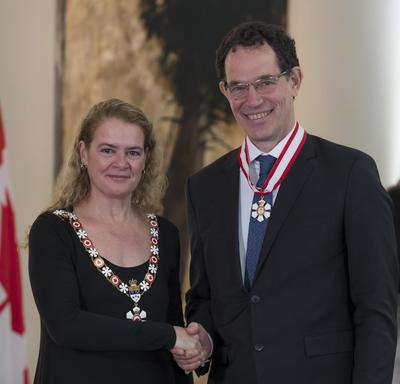 Neil G. Turok stands next to the Governor General.  Both smile at the camera.  They are wearing their Order of Canada insignia.