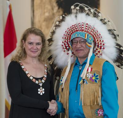 Edmund Metatawabin stands next to the Governor General.  Both smile at the camera.  They are wearing their Order of Canada insignia.