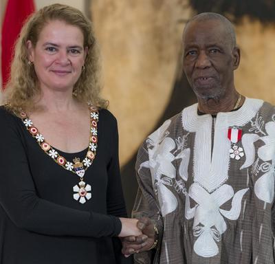 Lamine Touré se tient à côté de la Gouverneure générale.  Tous deux sourient à la caméra.  Ils portent leur insigne de l'Ordre du Canada.