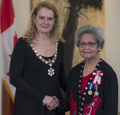 Marjorie White stands next to the Governor General.  Both smile at the camera.  They are wearing their Order of Canada insignia.