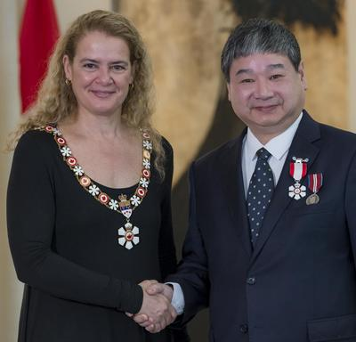 Yiyan Wu stands next to the Governor General.  Both smile at the camera.  They are wearing their Order of Canada insignia.