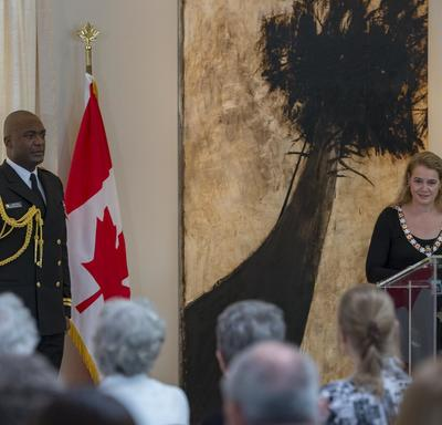 The Governor General stands behind a podium and faces a room full of people.  She delivers a speech.