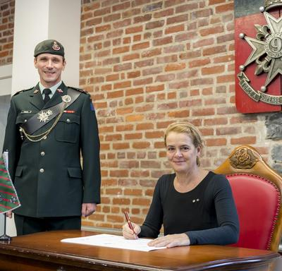 Governor General Julie Payette looks directly at the photographer, while she is sitting a table, pen in hand ready to sign a document. A men wearing a uniform is standing to her right.