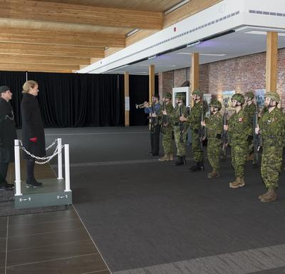 Governor General Julie Payette is standing on a dais and looks at an Honour Guard of two rows of 8 reservists in combat uniform.