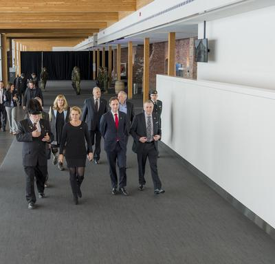 Governor General Julie Payette, accompanied by a group of about 10 people walk in the entrance hall of the Armoury of Les Voltigeurs de Québec.