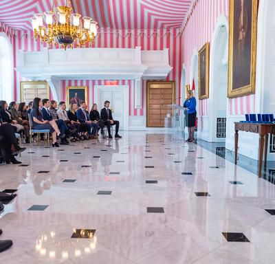 Side view of Ms. Assunta Di Lorenzo speaking at a podium in front of an audience in Rideau Hall's red, black and white tent room.