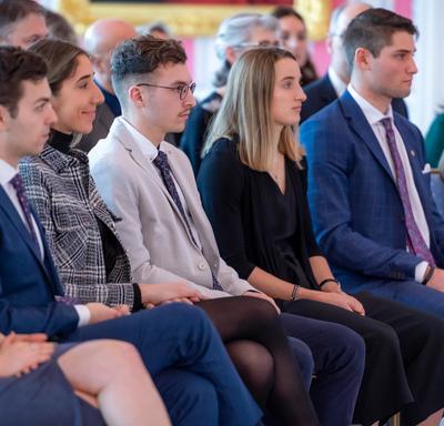 Vue latérale d'étudiants universitaires qui sont assis au premier rang d'une audience.