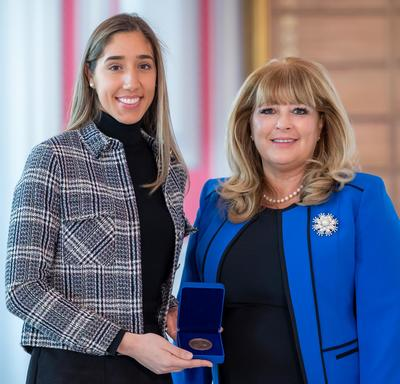 On the left, a tall female university student is holding an opened blue box containing a medal. A blond woman wearing a blue jacket is on the right.