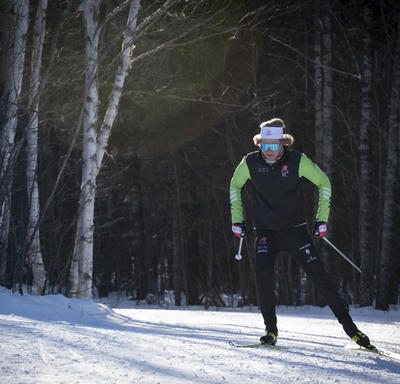 A competitive cross-country skier racing down a trail.