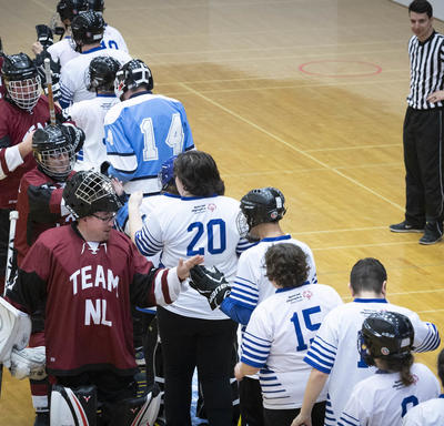 Two teams line up to shake hands after a hard-fought game.