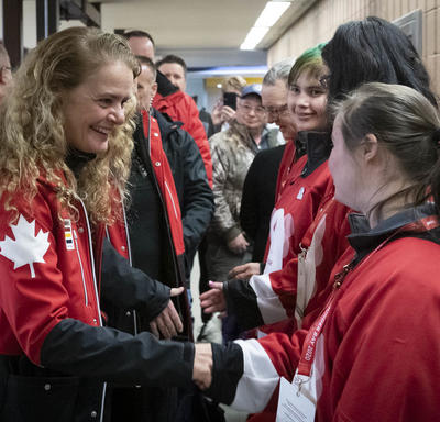 Dressed in Canada red, the Governor General shakes hands with Special Olympics athletes after their game.