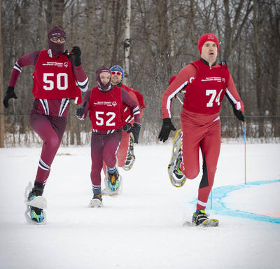 Athletes compete outdoors in a tight snowshoeing race.