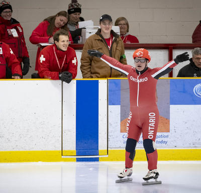 A speed skater raises his arms and readies to compete in the Special Olympics.
