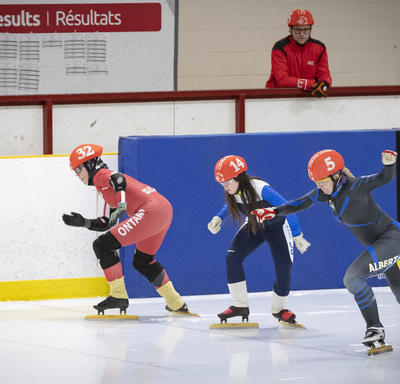 Athletes compete in a tight speed skating race.