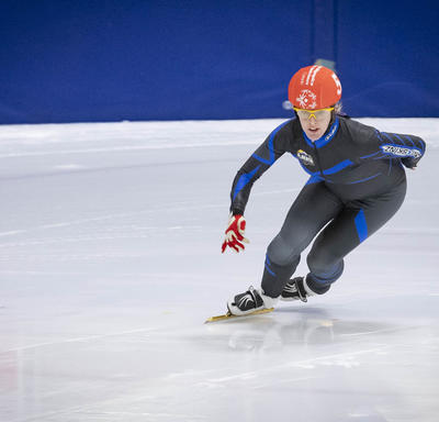 A speed skater takes a tight turn during a race at the Special Olympics.