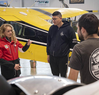 The Governor General in the Aviation Centre of Excellence hangar with students, teachers and aircraft.