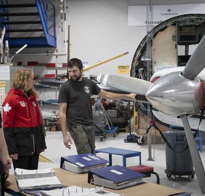 La gouverneure générale dans le hangar du Centre d'excellence en aviation avec des élèves, des enseignants et des avions.