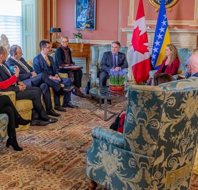 Canadian government officials and members of the Bosnia and Herzegovina delegation attend a meeting with the Governor General and His Excellency Željko Komšić. Everyone is sitting in chairs.