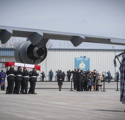 CAF members carry a coffin to the hearse. A bagpiper is in the forefront of the picture.