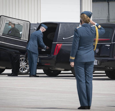 The Governor General salutes a coffin as it is placed in a hearse.