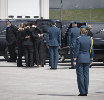 Family members of the deceased embrace each other beside a hearse.
