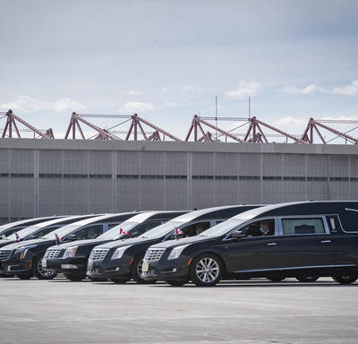 Six hearses are parked beside each other.