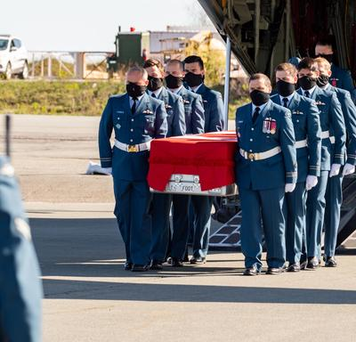 Captain Jennifer Casey's coffin is carried off the plane by Canadian Armed Forces members.