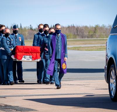 Captain Jennifer Casey's coffin is carried by Canadian Armed Forces members to the hearse. Leading the way is the chaplain.