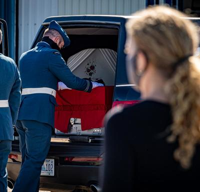 The Governor General and Commander-in-Chief of Canada stands as Captain Jennifer Casey's coffin is placed in the hearse.